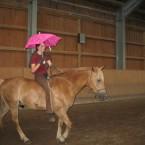 Wir reiten mit einem aufgespannten rosa Regenschirm