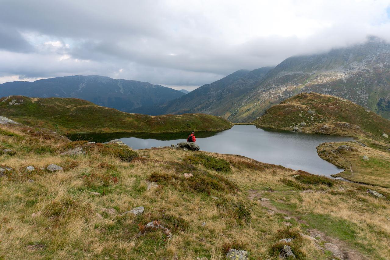 Wanderer sitzt auf einem Fels vor dem unteren Wildalmsee